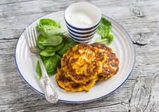 Sweet potato pancakes and fresh spinach. On a light wooden background stock image