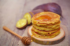 Sweet potato pancakes. Sweet potato pancakes with honey on wooden plate Royalty Free Stock Photos