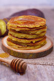 Sweet potato pancakes. Sweet potato pancakes with honey on wooden plate Royalty Free Stock Images