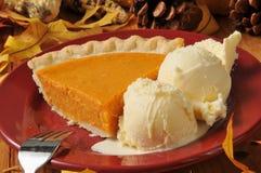 Sweet potato pie al a mode. A slice of sweet potato or pumpkin pie with vanilla ice cream stock photography