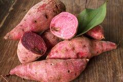 Sweet potato. Sweet purple potato on wood background royalty free stock images