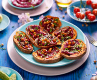 Sweet potato toast with beet hummus, grilled chickpeas, fresh parsley, nigella seeds and sunflower seeds on a plate on a blue ta. Vegetable toast with sweet stock photo