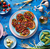 Sweet potato toast with beet hummus, grilled chickpeas, fresh parsley, nigella seeds and sunflower seeds on a plate on a blue ta. Vegetable toast with sweet royalty free stock image
