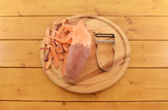 Sweet potato with vegetable peeler on a chopping board Royalty Free Stock Image
