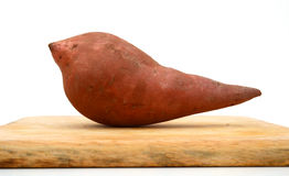 Sweet potato on wooden cutting board isolated on white Royalty Free Stock Photo