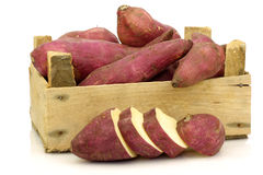 Sweet potatoes and a cut one in a wooden crate Stock Image