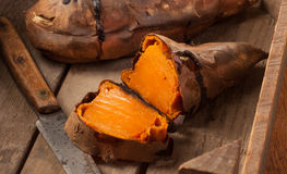 Sweet potatoes. Oven baked sweet potatoes on vintage wood royalty free stock photography