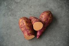 Sweet potatoes over dark table stock photos