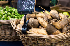 Sweet Potatoes. Whicker basket filled with sweet potatoes and a sign. Brussels Sprouts in a second basket in the background stock photos