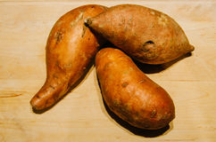 Sweet potatoes on wooden background Royalty Free Stock Images