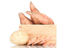 Sweet potatoes. In a wooden crate on a white reflective background Royalty Free Stock Photo