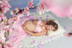 Sweet pregnancy. Beautiful pregnant woman surrounded by flowers Stock Photo