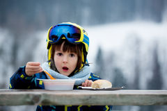 Sweet preschool child, eating soup in a restaurant on ski slope. Having a break from skiing Stock Image