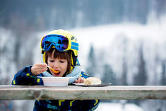 Sweet preschool child, eating soup in a restaurant on ski slope. Having a break from skiing Stock Photos