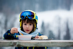 Sweet preschool child, eating soup in a restaurant on ski slope. Having a break from skiing Royalty Free Stock Photography