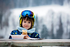 Sweet preschool child, eating soup in a restaurant on ski slope. Having a break from skiing Stock Photography