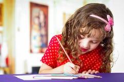 Sweet preschooler girl using colored pencils Royalty Free Stock Photos