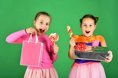 Sweet presents concept. Girls with excited faces pose with candies. And presents on green background. Sisters with lollipops, boxes and bags. Children eat big royalty free stock image