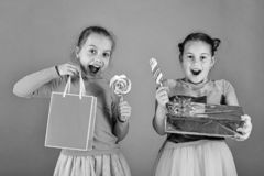 Sweet presents concept. Girls with excited faces pose with candies. And presents on green background. Sisters with lollipops, boxes and bags. Children eat big stock image