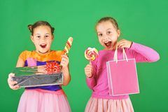 Sweet presents concept. Girls with excited faces pose with candies. And presents on green background. Sisters with lollipops, boxes and bags. Children eat big royalty free stock photos