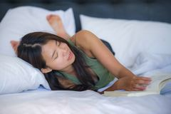 Sweet and pretty young Asian woman or teenager reading novel book in bed or studying relaxed lying on bed at home bedroom in comfo Royalty Free Stock Image
