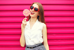Sweet pretty young woman with lollipop over pink stock photography