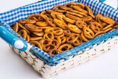 Sweet pretzels on a beautiful fabric in a wicker basket on a white background royalty free stock photography
