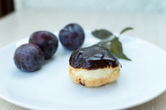 Sweet profiteroles with cream and chocolate glaze and plums on a Royalty Free Stock Photo