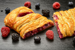 Sweet puff pastry with raspberries, blueberries, blackberries and cream cheese on black background. stock photo