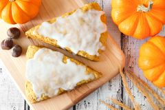 Sweet pumpkin scones with frosting, overhead view on wood Royalty Free Stock Image
