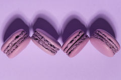 Sweet purple macaroons on purple table background. Royalty Free Stock Photography