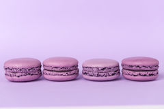Sweet purple macaroons on purple table background. Royalty Free Stock Images