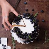 Sweet purrple berries cake with woman hand with fresh berries on wooden table top view stock photo