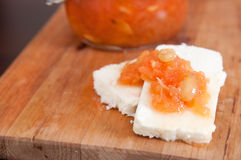 Sweet quince jam with almonds on white cheese. Selective focus Stock Image