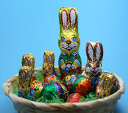Sweet rabbits and eggs in basket. On  blue background Royalty Free Stock Photo