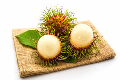 Sweet Rambutan fruit with leaves. Sweet Rambutan fruit with leaves on white background Royalty Free Stock Photography