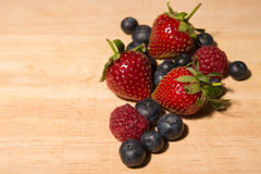 Sweet Raspberries, blueberries, strawberries on a wood plank Royalty Free Stock Images