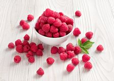 Sweet raspberries in bowl. On wooden table. Close up, high resolution product. Harvest Concept Stock Image