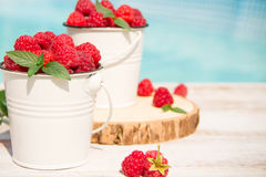 Sweet raspberries in bowl on wooden table. Close up, top view Stock Photo