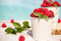 Sweet raspberries in bowl on wooden table. Stock Image