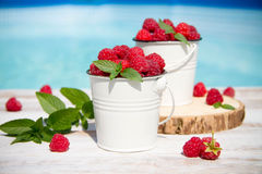 Sweet raspberries in bowl on wooden table. Close up, top view Stock Photos