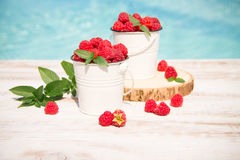 Sweet raspberries in bowl on wooden table. Stock Photo