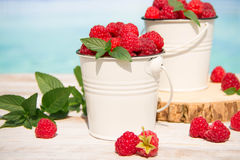 Sweet raspberries in bowl on wooden table. Royalty Free Stock Photos