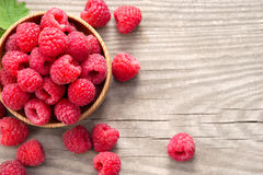 Sweet raspberries in bowl on wooden table. Close up, top view, high resolution product Royalty Free Stock Photo