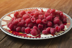 Sweet raspberries on plate. On wooden background.Fresh raspberry in ceramic plate on the wooden rustic desk Stock Photos