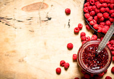Sweet raspberry jam in jar with spoon. On a wooden table Stock Photo