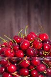 Sweet red cherries in glass bowl on dark wooden backgound with copy space. Summer and harvest concept. Vegan, vegetarian. Raw food Royalty Free Stock Photography