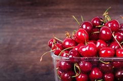 Sweet red cherries in glass bowl on dark wooden backgound with copy space. Summer and harvest concept. Vegan, vegetarian. Raw food Stock Images
