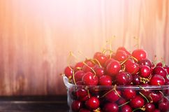 Sweet red cherries in glass bowl on dark wooden backgound with copy space. Sunny summer and harvest concept. Sunlight. Effect. Vegan, vegetarian, raw food Royalty Free Stock Image