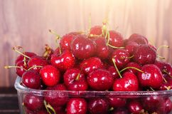 Sweet red cherries in glass bowl on dark wooden backgound with copy space. Sunny summer and harvest concept. Sunlight. Effect. Vegan, vegetarian, raw food Stock Image